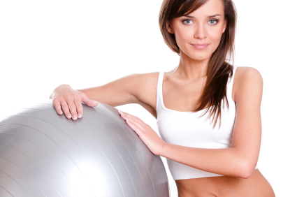 Young woman with pilates gym ball on white bacground